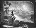 Young Kaiulani seated holding hat with backdrop of Diamond Head and palm trees in a studio, photograph by Menzies Dickson (PP-96-9-020).jpg