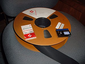 Videotape - A fourteen-inch reel of 2-inch quad videotape compared with a modern-day MiniDV videocassette. Both media store one hour of color video.
