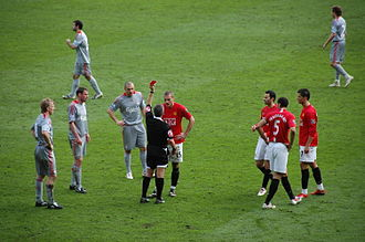 Referee (association football) - Referee Alan Wiley (black kit, centre) issues a red card to Manchester United's Nemanja Vidić