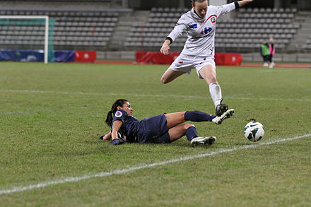 A player executing a slide tackle to dispossess an opponent 20121209 PSG-Juvisy - Kenza Dali 04.jpg