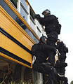 42nd Military Police Detachment's Special Reaction Team pull security on a bus 2005.jpg