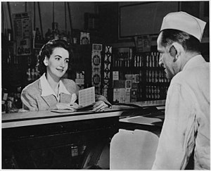 "A Customer Can Use the Ration Books of the Whole Family. But the First Thing She Will Want to Know When She Buys Pork Chops, Pound of Butter or a Half Pound of Cheese Is - ""How Many Points Will It Take?"" 1941 - 1945 (4545457453).jpg"