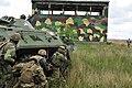 A Ukrainian Soldier returns fire from behind a BTR-80.jpg