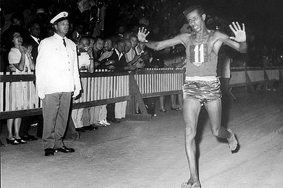 Abebe Bikila crossing the finish line, barefoot with hands raised, an Italian official in the background with a crowd of spectators behind a fence