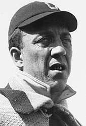 "A man with a lazy right eye is shown from the shoulders up. He is wearing a dark baseball cap on his head with a ""C"" on the front. His mouth is slightly open showing dirty teeth."