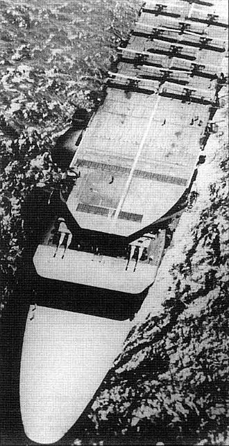 Japanese aircraft carrier Akagi - Akagi underway in 1929 with aircraft on the upper flight deck and two gun turrets on the middle flight deck