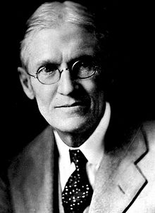 Black and white head-and-shoulders photo of silver-haired Andrew Sledd in glasses, suit jacket and tie