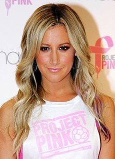 "Ashley Tisdale. A woman with long blonde hair wearing a white t-shirt with ""PROJECT PINK"