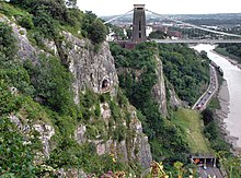 Rocky side to a gorge with a platform in front of a cave halfway up. To the right are a road and river. In the distance are a suspension bridge and buildings.