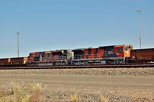 Distributed power - BHP Billiton Iron Ore EMD SD70ACe no. 4345 (left) and GE CM40-8 no. 5647 Abydos (right), marshalled as distributed power units, in a loaded iron ore train at Nelson Point yard, Port Hedland, Western Australia, April 2012.