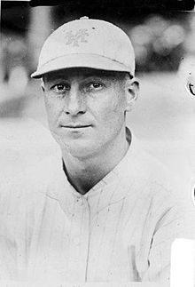 A man in a white pinstriped baseball uniform with a white baseball cap.