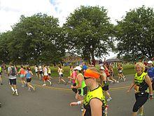 Mucha gente corriendo un maratón en la calle.  Hay árboles al fondo.