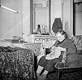 Bordurende vrouw gezeten in een fauteuil in haar woonkamer, Bestanddeelnr 252-9339.jpg