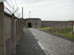View of a fort in the distance with a chain-link fence to the left