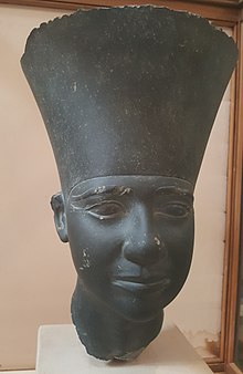 Black statue of a head wearing a large crown