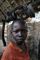 A boy playing with a burnt lamp in the city of Birao, Central African Republic. The town was almost completely burnt down in March 2007 during fighting between rebels and government troops.