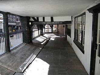 Chester Rows - Inside Watergate Street Row, showing premises on the right and space for stalls and the railings overlooking the street on the left