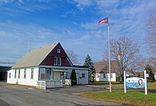 "At left, a wooden one-story building with a tall gabled roof. The ground level is white with green trim; the upper level a dark reddish-brown, also with green trim. In the middle is a flagpole with the American flag; behind it is a white church partially obscured by a bare tree. At right is a blue and white sign with ""Clermont"" prominent on it"