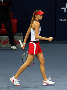 Daniela Hantuchova in a white top and red & white shorts, red cap, walking on a blue indoor surface