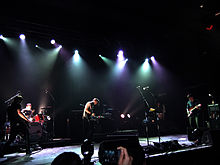 The members of a band perform a song under multi-colored stage lights