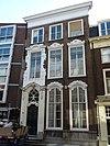 foto van Pand met bijzonder rijke toepassing van de Lodewijk XIV stijl versierde ingangstravee en kuifstukken boven de vensters, natuurstenen stoep