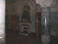 Picture of Dobroyd Castle's Saloon showing the marble pillars, clock, arched mirror and fireplace.
