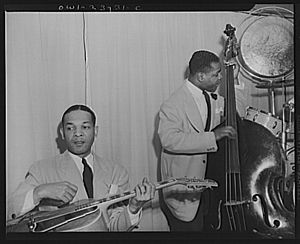 Jazz guitarist - Duke Ellington's big band at the Hurricane Ballroom had a rhythm section that included a jazz guitarist, a double bass player, and a drummer (not visible, but who is to the right of the bassist).
