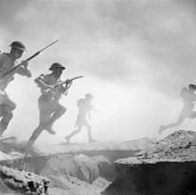period photo of helmeted soldiers with rifles running through dust and smoke