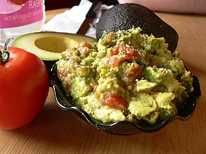 A bowl of guacamole beside a tomato and a cut ...