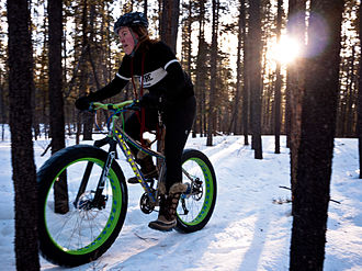 Cold-weather biking - A fatbike with wide, low-pressure tires being ridden over the snow