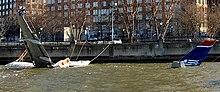 Photo montrant l'avion au premier plan amarré à une jetée, partiellement submergé dans le fleuve Hudson. Il est relié par des câbles à la berge et seule sa queue et son aile gauche sont clairement visibles, le reste de son corps se trouvant sous l'eau.