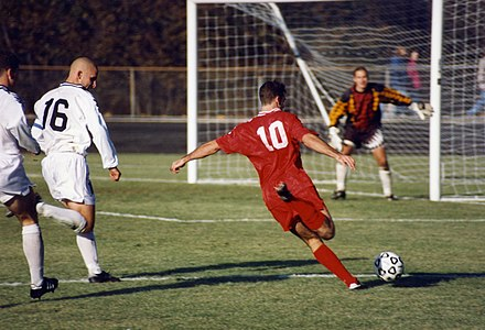 The striker (wearing the red shirt) is past the defence (in the white shirts) and is about to take a shot at the goal. Football iu 1996.jpg