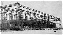 A ship's hull sits within the skeleton of a gantry crane