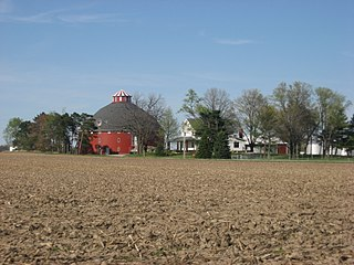 Round red barn and farmhouse