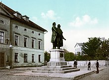 A bronze statue of two men stands on a stone pedestal. The statue is in the middle of a city square; on the left is the facade of a building. Three people are standing in the square and looking at the statue; the bronze statues are noticeably larger than life-sized.