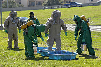 Dangerous goods - An emergency medical technician team training as rescue (grey suits) and decontamination (green suits) respondents to hazardous material and toxic contamination situations.