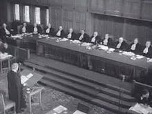 One man at a lectern addressing a large panel of judges