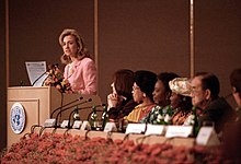 "Clinton speaking at a podium with several onlookers. She is delivering her ""human rights are women's rights and women's rights are human rights"" speech in Beijing during September 1995."