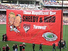 A red banner featuring drawings of former Essendon player James Hird and former coach Kevin Sheedy