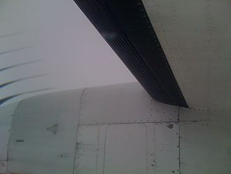 Icing conditions - Wing of a Bombardier Dash 8 Q400 passenger aircraft.  The black rubber deicing boot is inflated with air, producing ridges to crack and dislodge any accumulated ice.