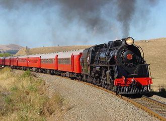 NZR 56-foot carriage - NZR JA class steam loco hauling two NZR 56-foot carriages followed by several NZR 50-foot carriages on an excursion train