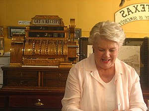 Hico, Texas - Hico museum employee Jan Canup stands in front of a gold-plated cash register retrieved from an old barn.