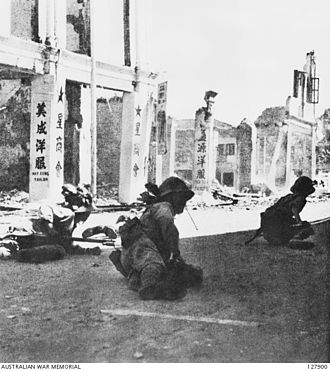 Malayan Campaign - Troops of the Imperial Japanese Army crouch on a street in Johore Bahru in the final stages of the Malayan Campaign.