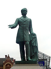 A statue depicting a mustachioed man holding an overcoat in his left hand with his right hand extended