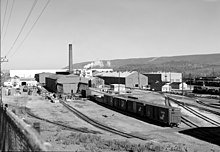Black-and-white photo showing tracks and box cars waiting outside rows of rectangular shop buildings, one with a smoke stack.
