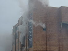Upper portion of brick building with smoke pouring from windows