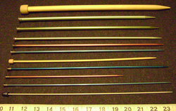 Knitting needles in a variety of sizes (US 2, 4, 5, 6, 7, 8, 9, 10, 11, 13 and 15 from the bottom).  The US size 7 and 15 needles are bamboo and wood, respectively, whereas the others are aluminum.  Having a smoother surface, metal needles tend to produce faster knitting but stitches are more likely to slide off by accident.
