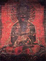 Frontal view of a fierce looking black deity surrounded by flames.