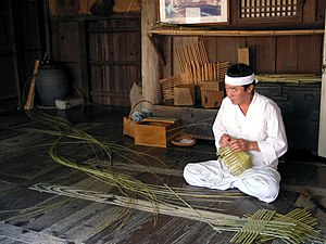 Yangdong Folk Village - A man in hanbok, traditional Korean costume weaving a basket in Yangdong village