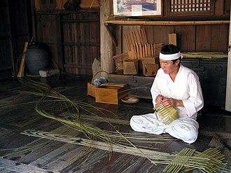 Yangdong Folk Village - A man in hanbok, traditional Korean costume weaving a basket in Yangdong village